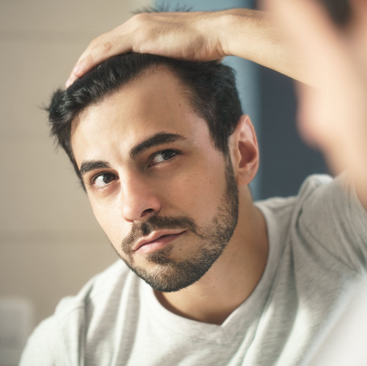Man looking in mirror at hair